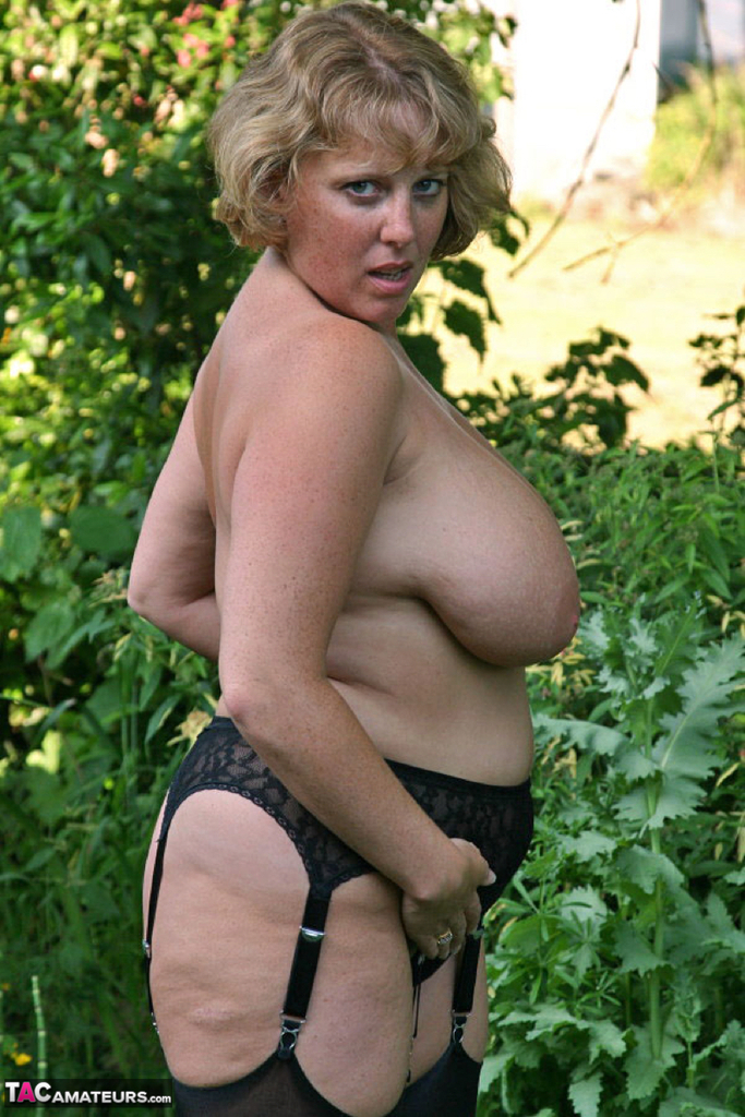 Big boobed milf takes her knickers off in the garden and shows her pussy